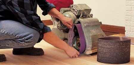 Houten vloer schuren met parketschuurmachine, band verwisselen